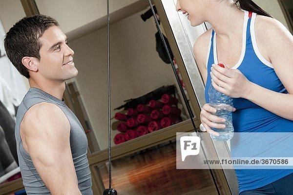 Ausübung in ein Fitness-Studio mit einer Frau neben ihm lächelnd mann