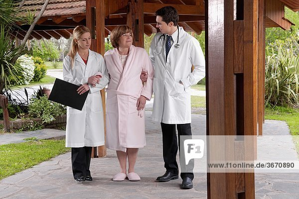 Doctors assisting a patient in walking in a rehabilitation centre