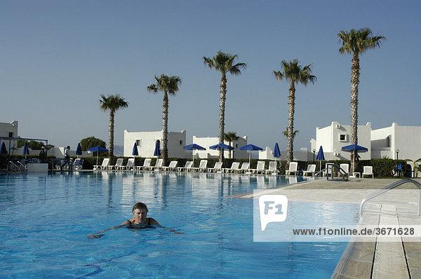 Aktive Senioren Frau schwimmt im Waaser eines Pools mit Palmen im Hintergrung Hotel Aeolos Beach Insel Kos Griechenland