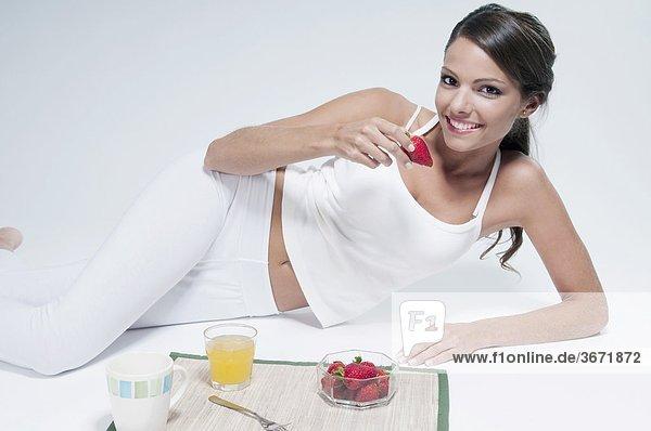 Frau auf dem Boden liegen und Erdbeeren Essen
