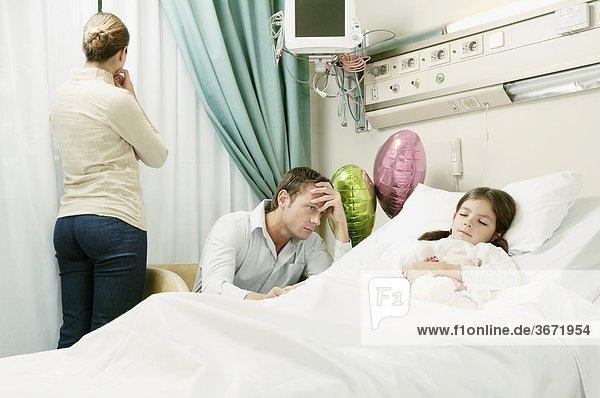 Mädchen auf einem Krankenhausbett mit ihren Eltern neben ihr