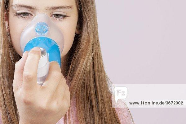 Mädchen mit ein Asthma-Inhalator verbunden mit spacer