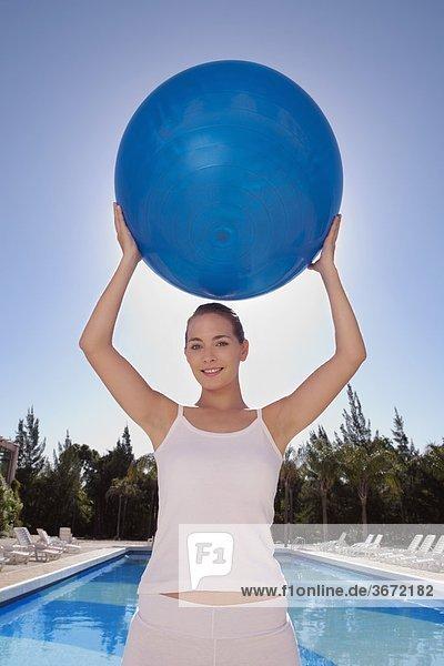 Frau Sport halten Beckenrand Ball Spielzeug