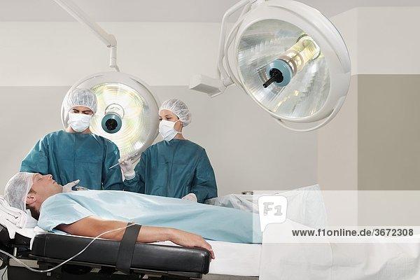 Zwei Chirurgen Betrieb ein Patient in einem OP-Saal