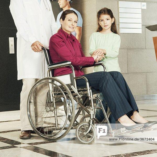Doktor Druck eine Frau in einem Rollstuhl