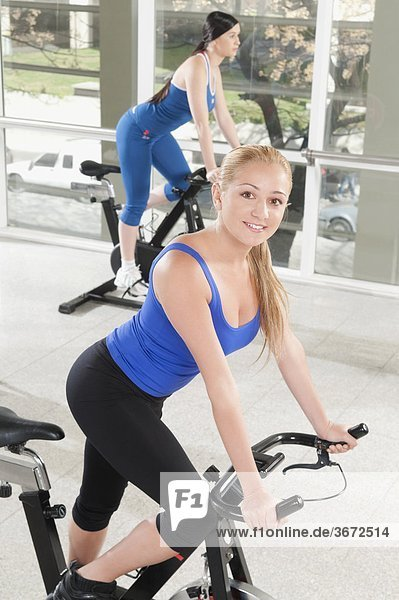 Zwei Frauen aus auf Fahrrädern in einer Turnhalle