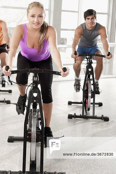 Drei Menschen auf Fahrrädern in einer Turnhalle Ausarbeitung