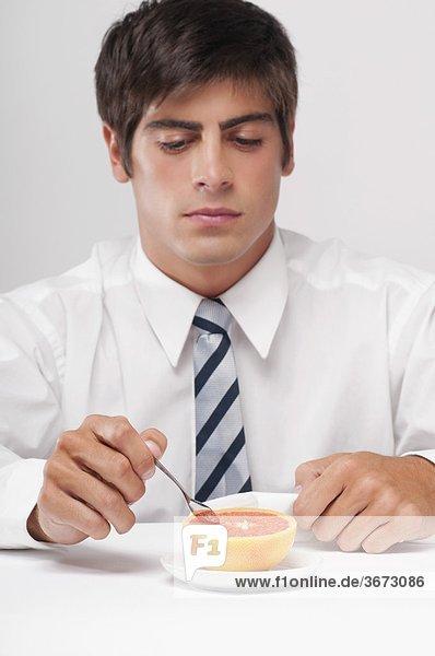 Nahaufnahme eines Kaufmanns Essen Grapefruit mit einem Löffel