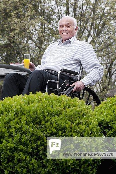 sitzend Portrait Mann Glas halten Saft Rollstuhl