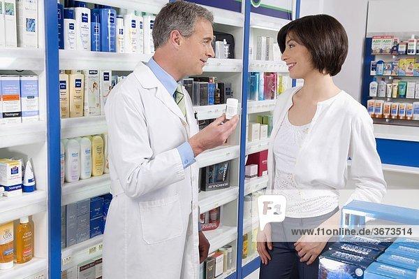 Apotheker hält eine Flasche Medizin und Beratung mit Kunden