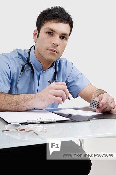 Portrait of a doctor writing a prescription