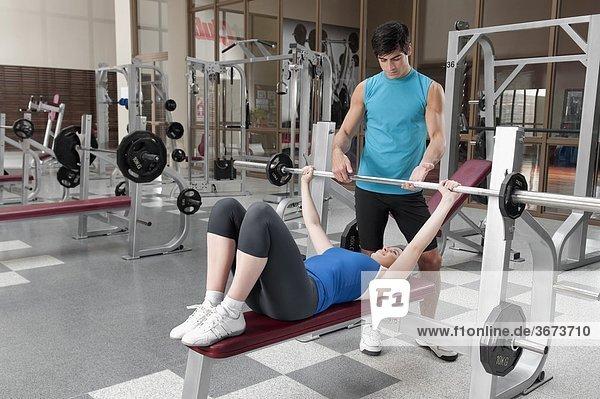 Gewicht-Training eine Frau bei männlichen instructor