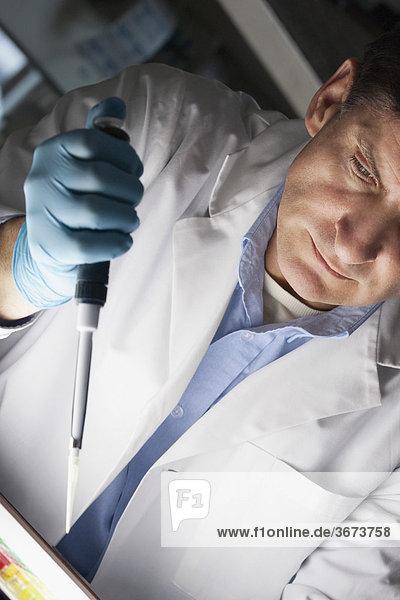 Arzt mit eine Pipette in einem Labor
