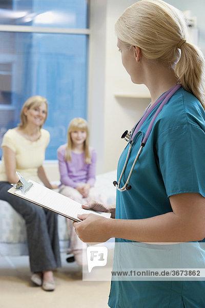 Eine Zwischenablage mit Patienten im hintergrund hält ärztin