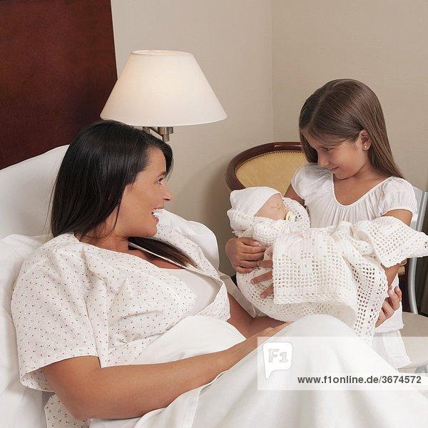 Frau mit ihrem Neugeborenen Baby und ihrer Tochter in einem Krankenhaus