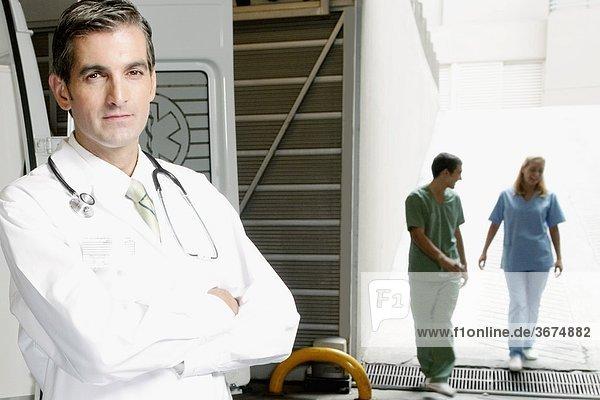 Portrait eines Arztes mit Krankenschwestern im Hintergrund