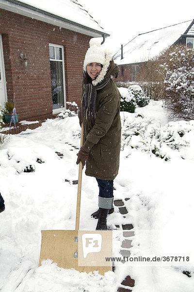 Frau schiebt schnee