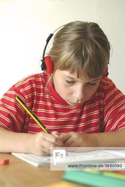 Kind macht hausaufgaben mit Musik/ child does her homework listening to music