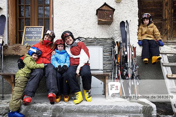 Familie sitzend vor der Scheune mit Skiern