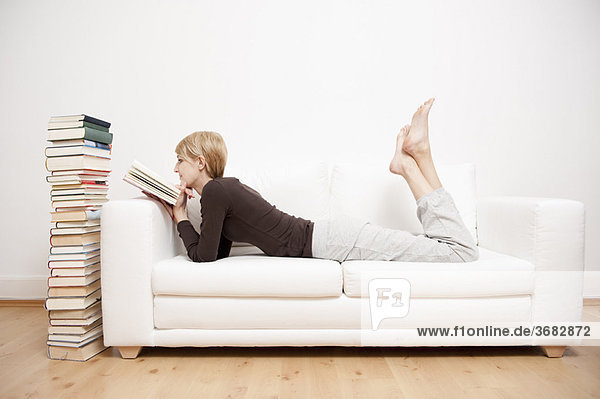 Woman reading a book on sofa