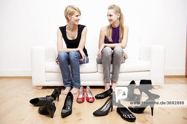 Women on sofa surrounded by shoes