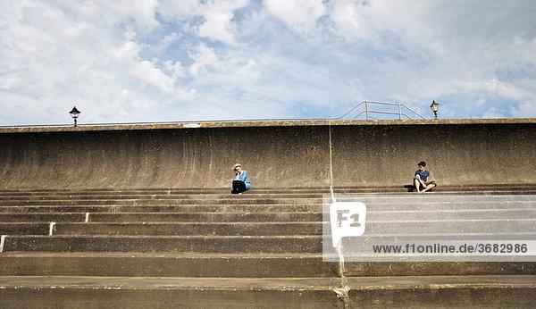 Mann und Frau sitzen getrennt auf einer Treppe