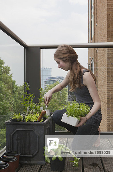 Junge Frau im Garten auf dem Balkon
