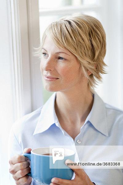 Junge Frau zu Hause mit Pokal