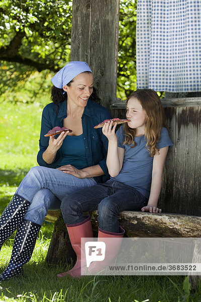 Mother and daughter resting on shed
