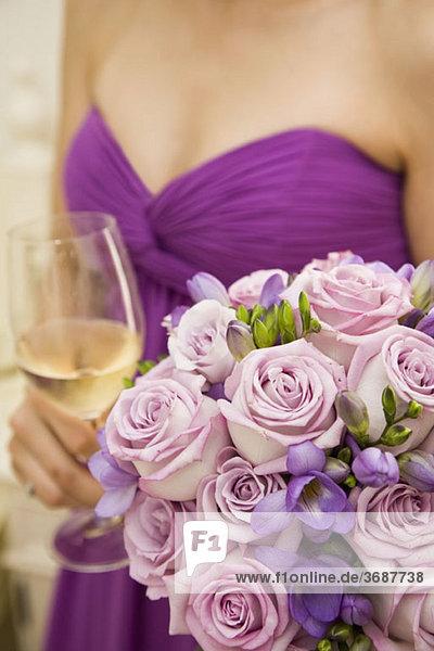 Mittelteil einer Brautjungfer  die einen Blumenstrauß und ein Glas Wein hält.
