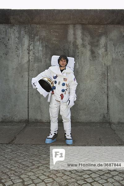 Ein Astronaut steht auf einem Bürgersteig in einer Stadt.