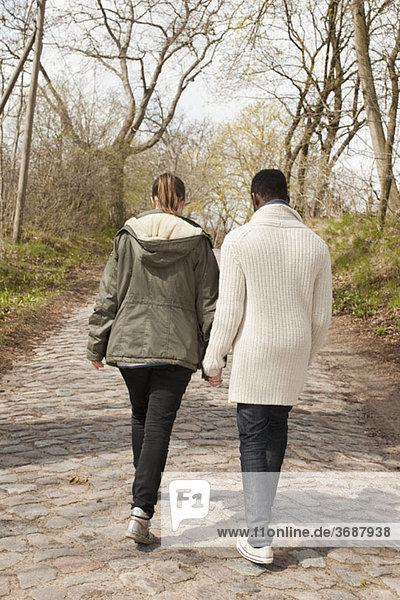 Ein junges Paar  das auf einer Kopfsteinpflasterstraße unterwegs ist.