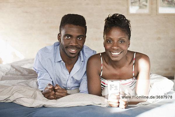 Ein junges Paar entspannt im Bett