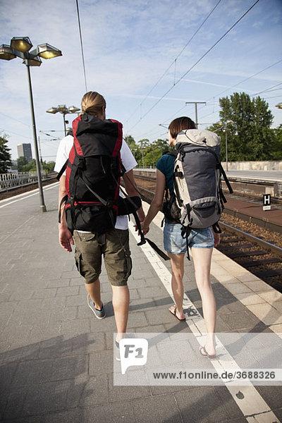 Ein Backpacker-Paar  das einen Bahnsteig hinuntergeht.