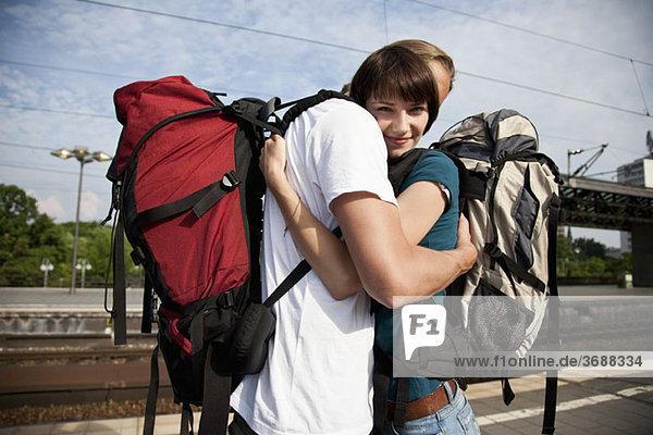 Eine junge Frau umarmt ihren Freund auf einem Bahnsteig.