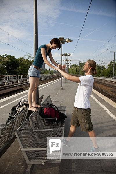 Ein junges Paar beim Warten auf dem Bahnsteig