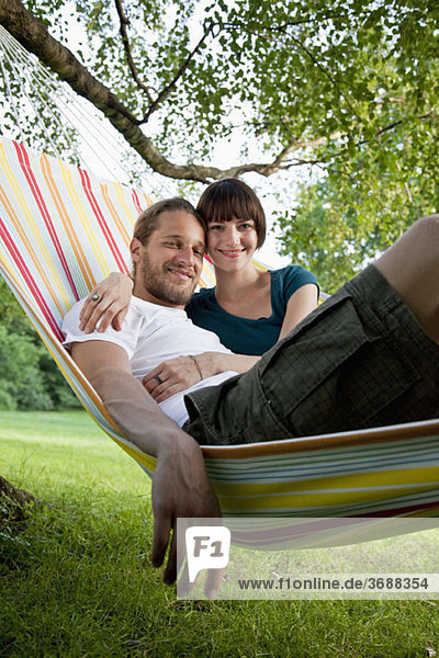A young happy couple lying in a hammock together