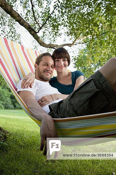 Ein junges glückliches Paar  das zusammen in einer Hängematte liegt.