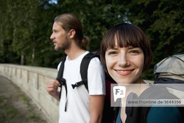 Eine junge Backpackerin mit ihrem Freund  die sich auf die Frau konzentriert.