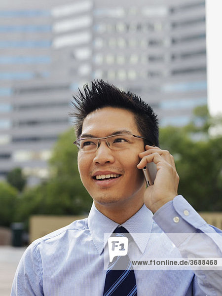 A smiling businessman using a mobile phone