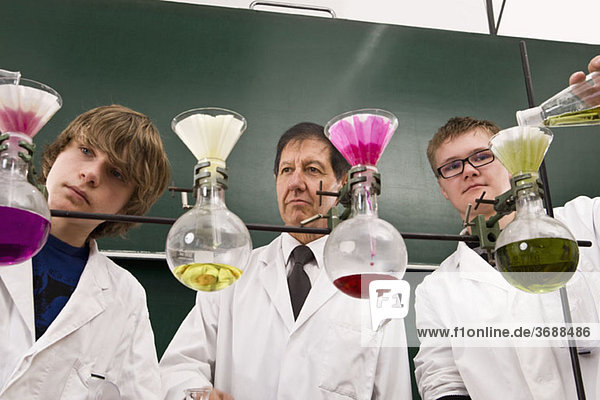 A teacher supervising two students conducting a chemistry experiment