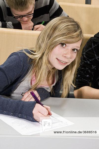 Porträt eines Teenagers  der ein Arbeitsblatt in der Klasse macht  lächelnd vor der Kamera.