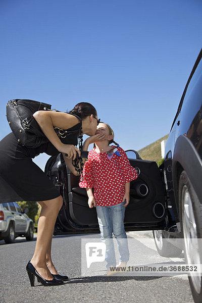 Eine Frau  die ein Mädchen küsst  das neben einem Auto steht.