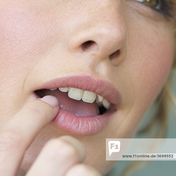 Detail einer Frau  die ihre Lippe mit dem Finger berührt.