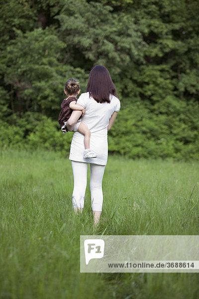 Eine Frau mit ihrer kleinen Tochter  Rückansicht  im Freien