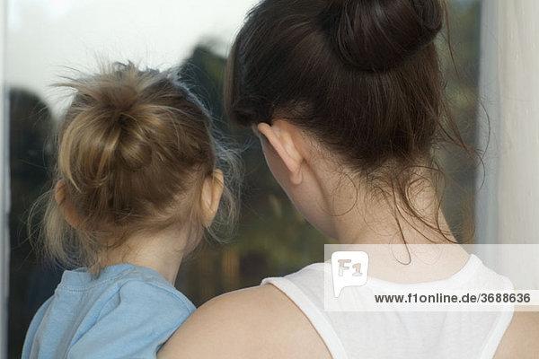 Eine junge Frau hält ihre kleine Tochter.
