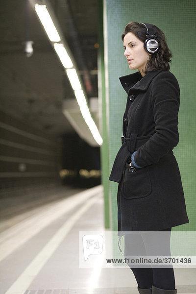Frau mit Kopfhörern in der U-Bahn
