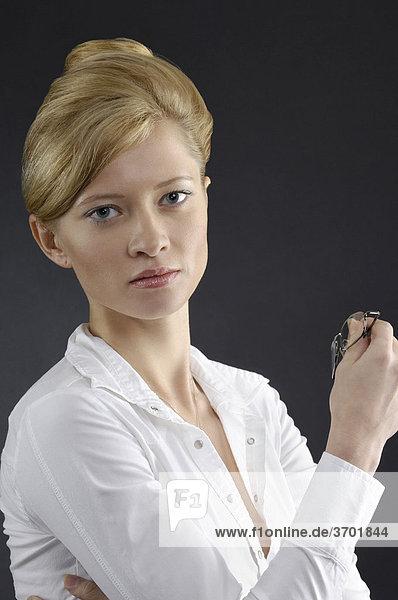 Porträt einer jungen Geschäftsfrau mit Brille in der Hand