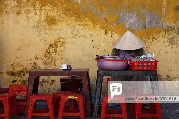 Eine vietnamesische Frau wartet auf Kundschaft an ihrem Straßenstand  Hoi An  Vietnam  Südostasien