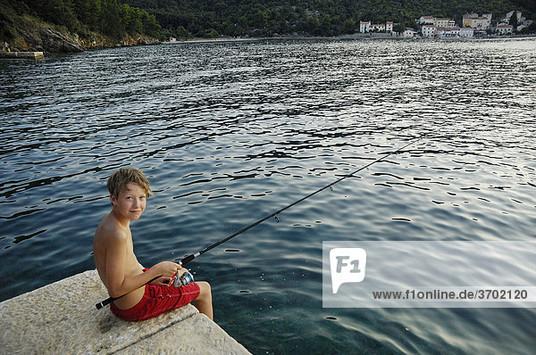 13jähriger Junge sitzt beim Angeln auf Mole  Bucht von Valun  Insel Cres  Kroatien  Europa